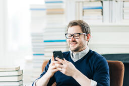 Man Studying on an iPhone in a Living Room Full of Books  image 5