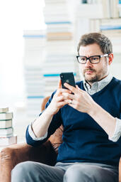 Man Studying on an iPhone in a Living Room Full of Books  image 6
