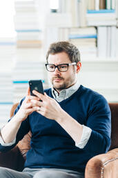 Man Studying on an iPhone in a Living Room Full of Books  image 3