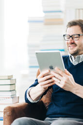 Man Studying on an iPad in a Living Room Full of Books  image 12