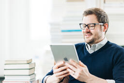 Man Studying on an iPad in a Living Room Full of Books  image 11