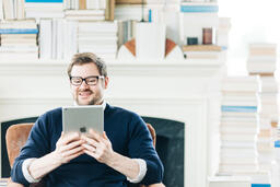Man Studying on an iPad in a Living Room Full of Books  image 7
