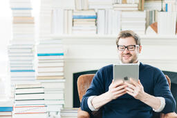 Man Studying on an iPad in a Living Room Full of Books  image 8