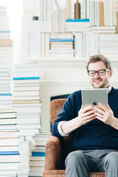Man Studying on an iPad in a Living Room Full of Books  image 10