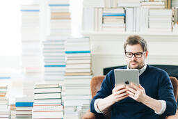 Man Studying on an iPad in a Living Room Full of Books  image 6