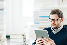 Man Studying on an iPad in a Living Room Full of Books  image 5
