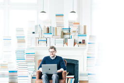 Man Studying on a Laptop in a Living Room Full of Books  image 3