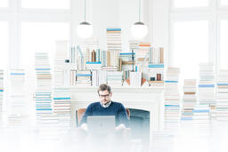 Man Studying on a Laptop in a Living Room Full of Books  image 2