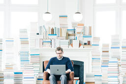 Man Studying on a Laptop in a Living Room Full of Books  image 1