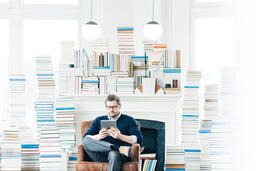 Man Studying on an iPad in a Living Room Full of Books  image 3