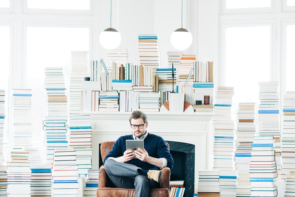 Man Studying on an iPad in a Living Room Full of Books large preview