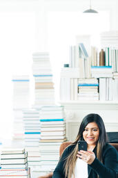 Woman Studying on an iPhone in a Living Room Full of Books  image 6
