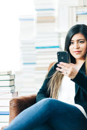 Woman Studying on an iPhone in a Living Room Full of Books  image 8