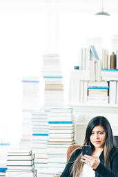 Woman Studying on an iPhone in a Living Room Full of Books  image 12