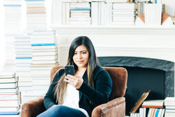 Woman Studying on an iPhone in a Living Room Full of Books  image 10