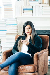 Woman Studying on an iPhone in a Living Room Full of Books  image 11