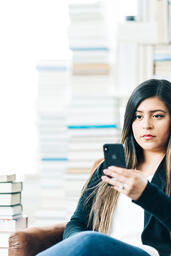 Woman Studying on an iPhone in a Living Room Full of Books  image 2
