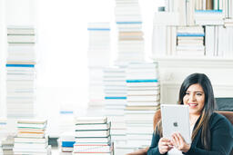 Woman Studying on an iPad in a Living Room Full of Books  image 3