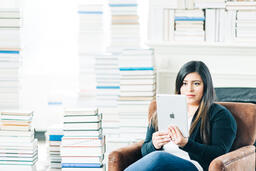 Woman Studying on an iPad in a Living Room Full of Books  image 1