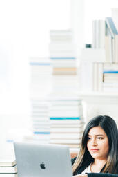 Woman Studying on a Laptop in a Living Room Full of Books  image 1
