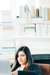 Woman Studying on a Laptop in a Living Room Full of Books  image 10