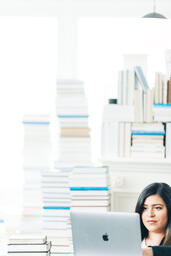 Woman Studying on a Laptop in a Living Room Full of Books  image 7