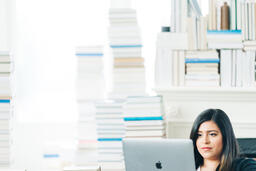 Woman Studying on a Laptop in a Living Room Full of Books  image 5
