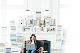 Woman Studying on a Laptop in a Living Room Full of Books  image 2