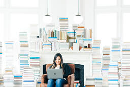 Woman Studying on a Laptop in a Living Room Full of Books  image 3