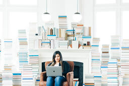 Woman Studying on a Laptop in a Living Room Full of Books  image 8