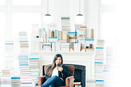 Woman Studying on an iPhone in a Living Room Full of Books  image 3
