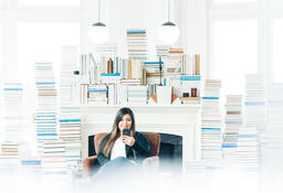Woman Studying on an iPhone in a Living Room Full of Books  image 4