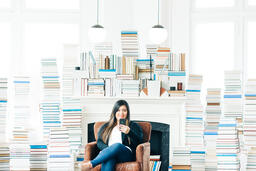 Woman Studying on an iPhone in a Living Room Full of Books  image 5