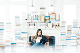 Woman Studying on an iPhone in a Living Room Full of Books  image 1