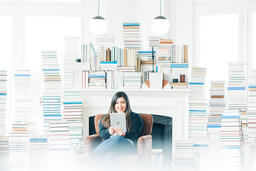 Woman Studying on an iPad in a Living Room Full of Books  image 2