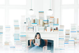 Woman Studying on an iPad in a Living Room Full of Books  image 6