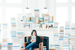 Woman Studying on an iPad in a Living Room Full of Books  image 5