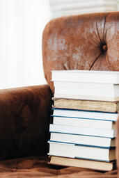 A Stack of Books on a Chair Surrounded by Books  image 2
