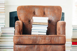 A Stack of Books on a Chair Surrounded by Books  image 3