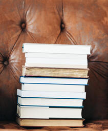 A Stack of Books on a Chair Surrounded by Books  image 4