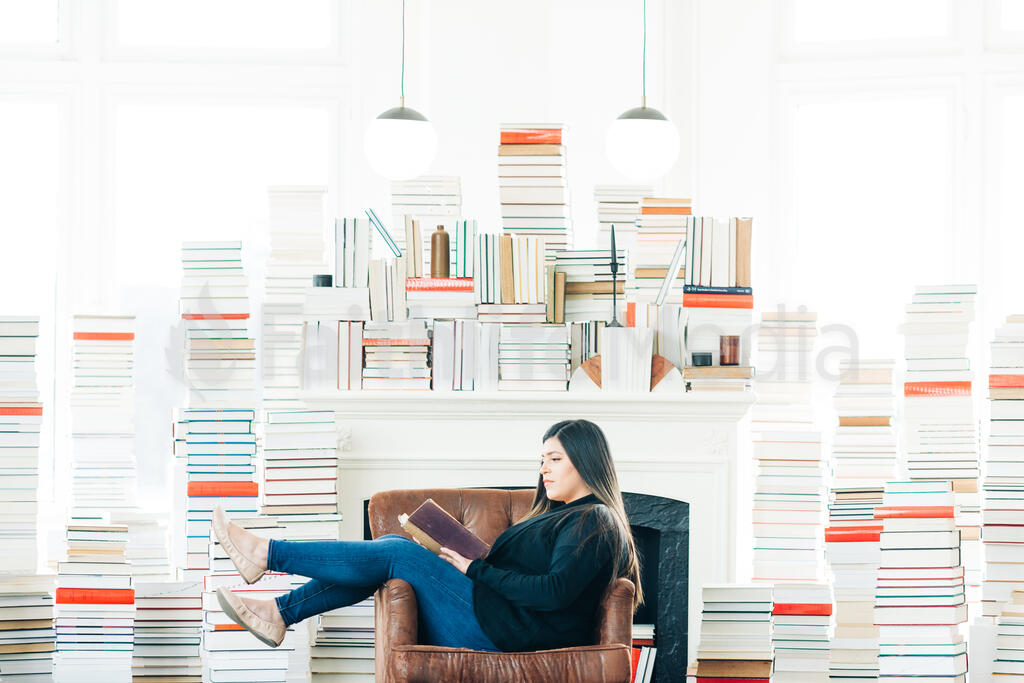 A Woman Reading Surrounded by Stacks of Books large preview