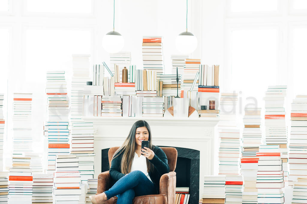 A Woman Studying on an iPhone in a Living Room Full of Books large preview
