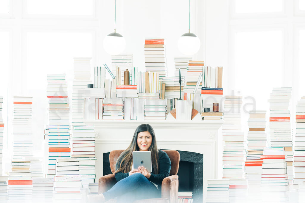 A Woman Studying on an iPad in a Living Room Full of Books large preview