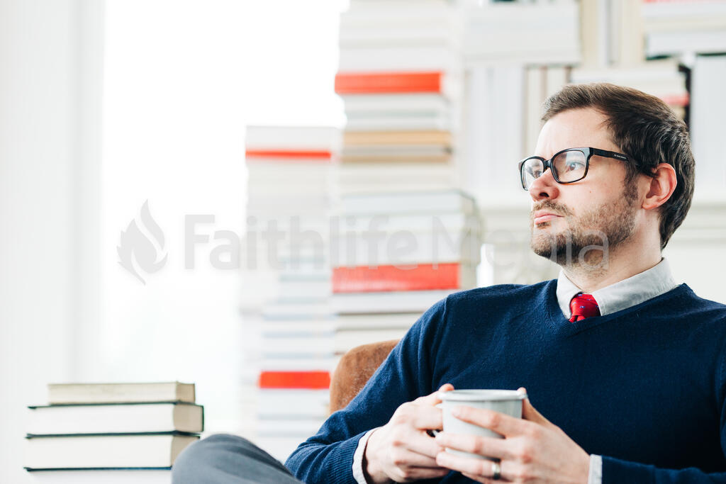 Man Drinking Coffee in a Room Full of Books large preview