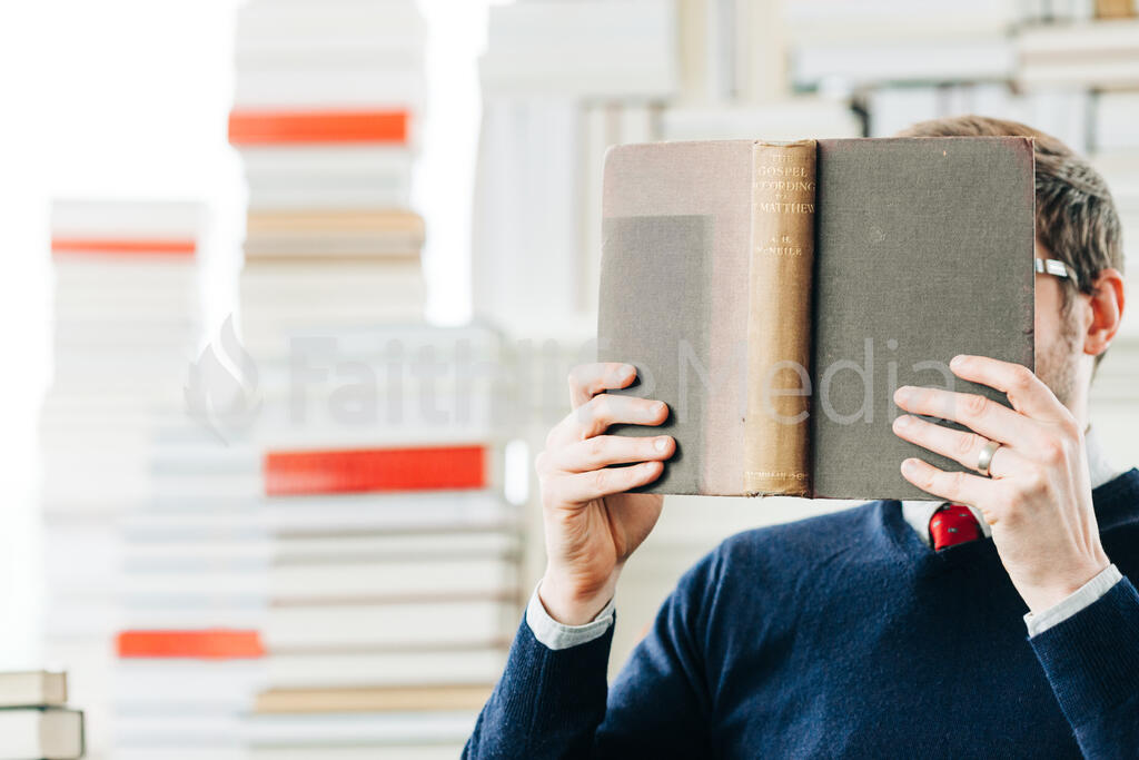 Man Reading a Book in a Living Room Full of Books large preview