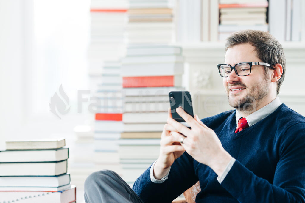 Man Studying on an iPhone in a Living Room Full of Books large preview