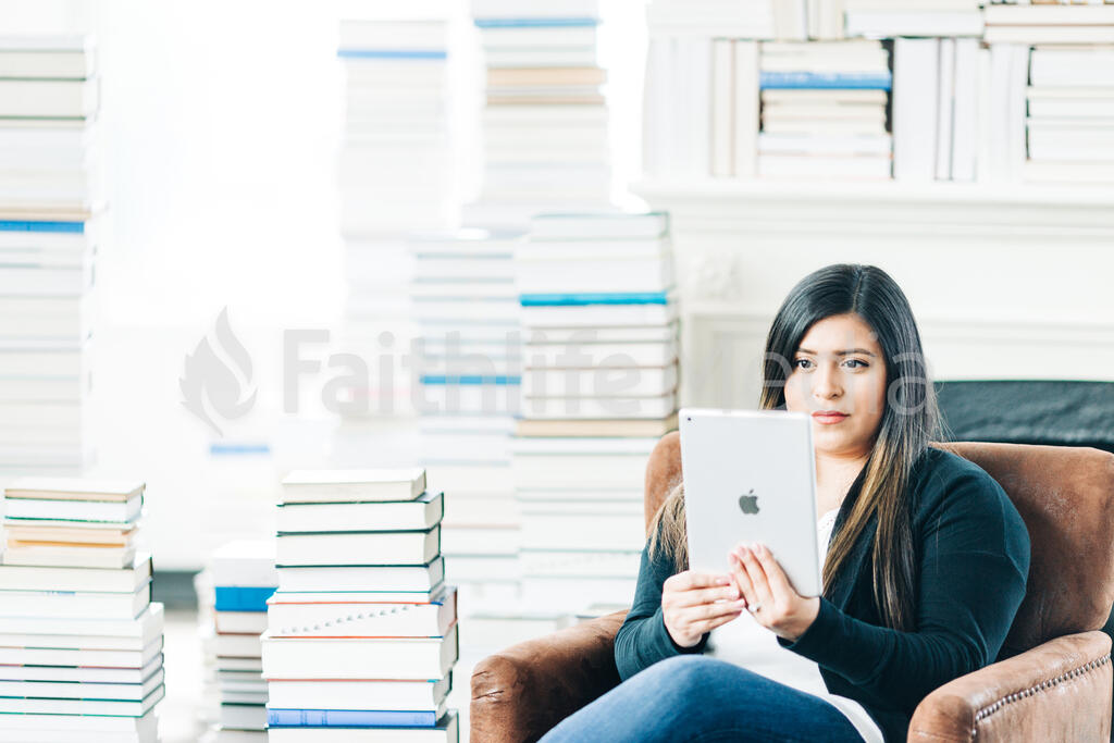 Woman Studying on an iPad in a Living Room Full of Books large preview
