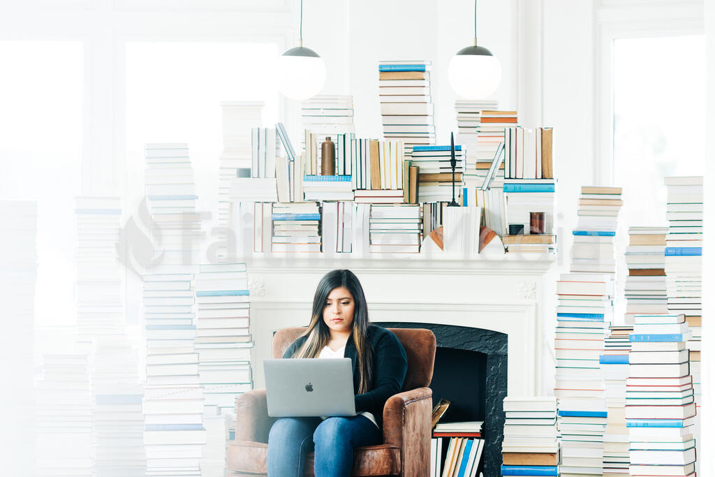 Woman Studying on a Laptop in a Living Room Full of Books large preview
