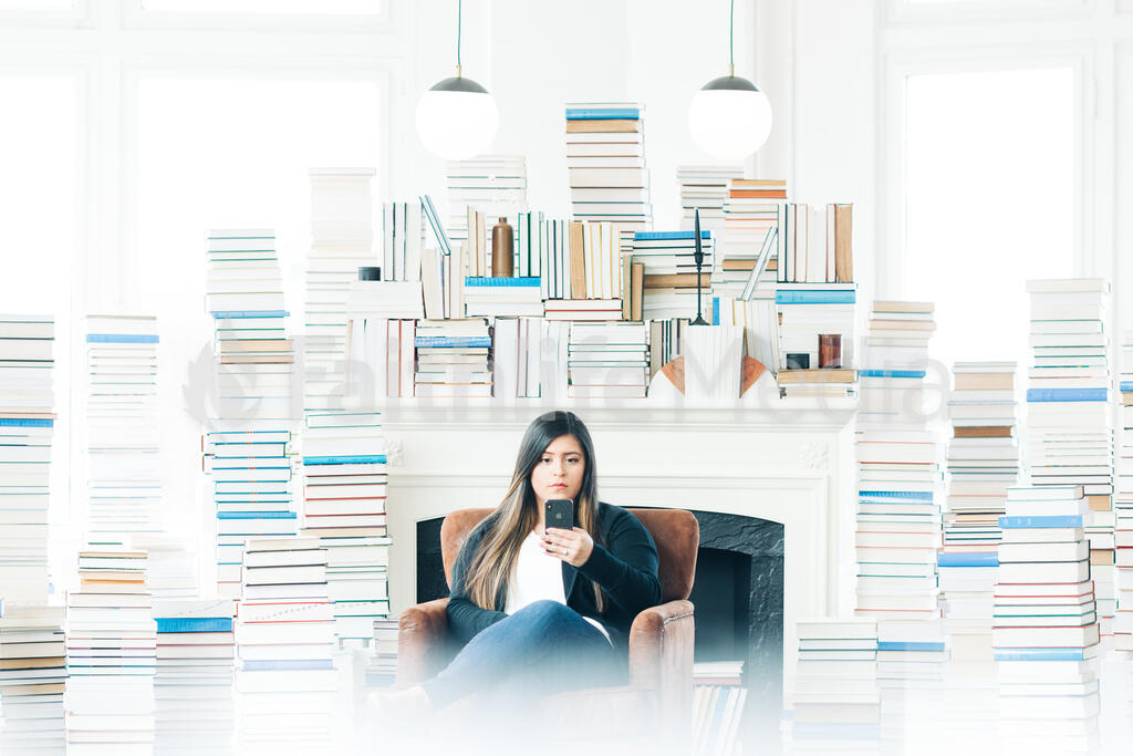 Woman Studying on an iPhone in a Living Room Full of Books large preview