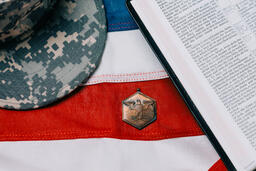 Military Hat and Open Bible on an American Flag  image 1